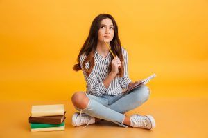 Portrait Of Pensive Young Girl Making Notes